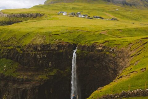 man standing on cliff watching punch bowl waterfalls
